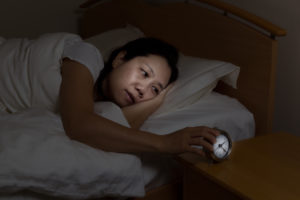 woman watching alarm clock while eyes open.