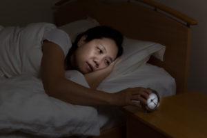 woman watching alarm clock while eyes open.