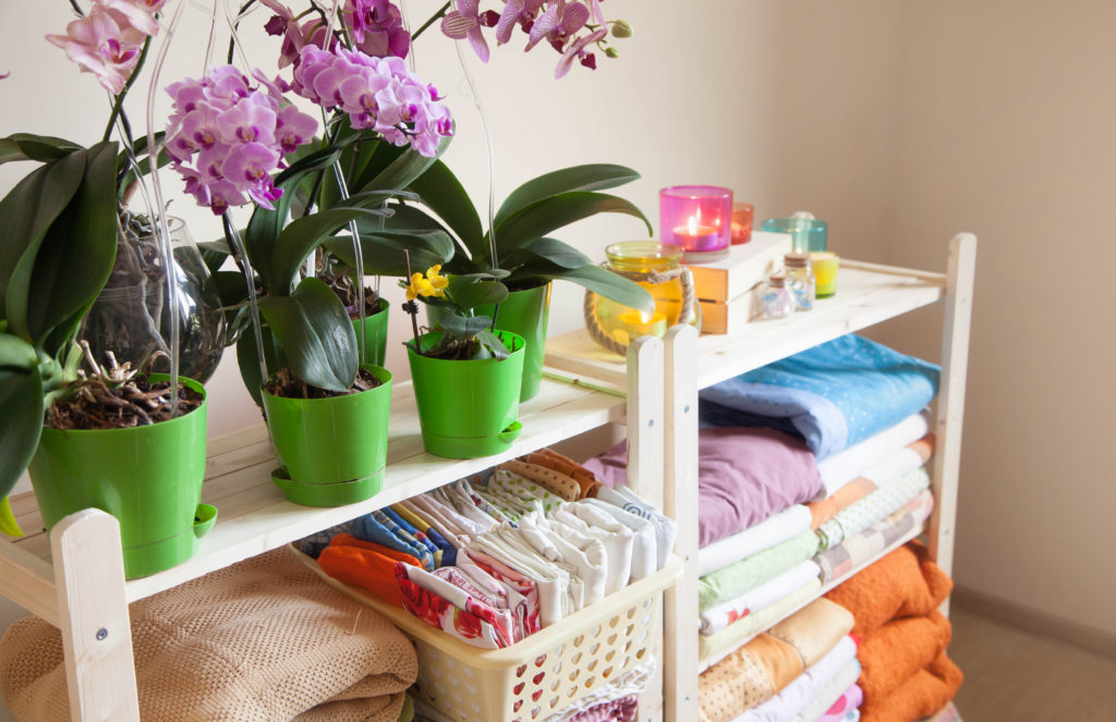 The girl puts the bed linen in the closet. Phalaenopsis orchids stand on the shelf. KonMari Marie Kondo organized shelves
