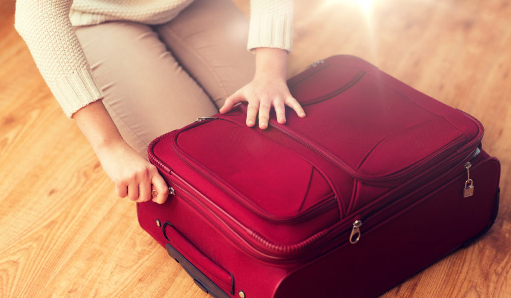 woman packing a red suitcase