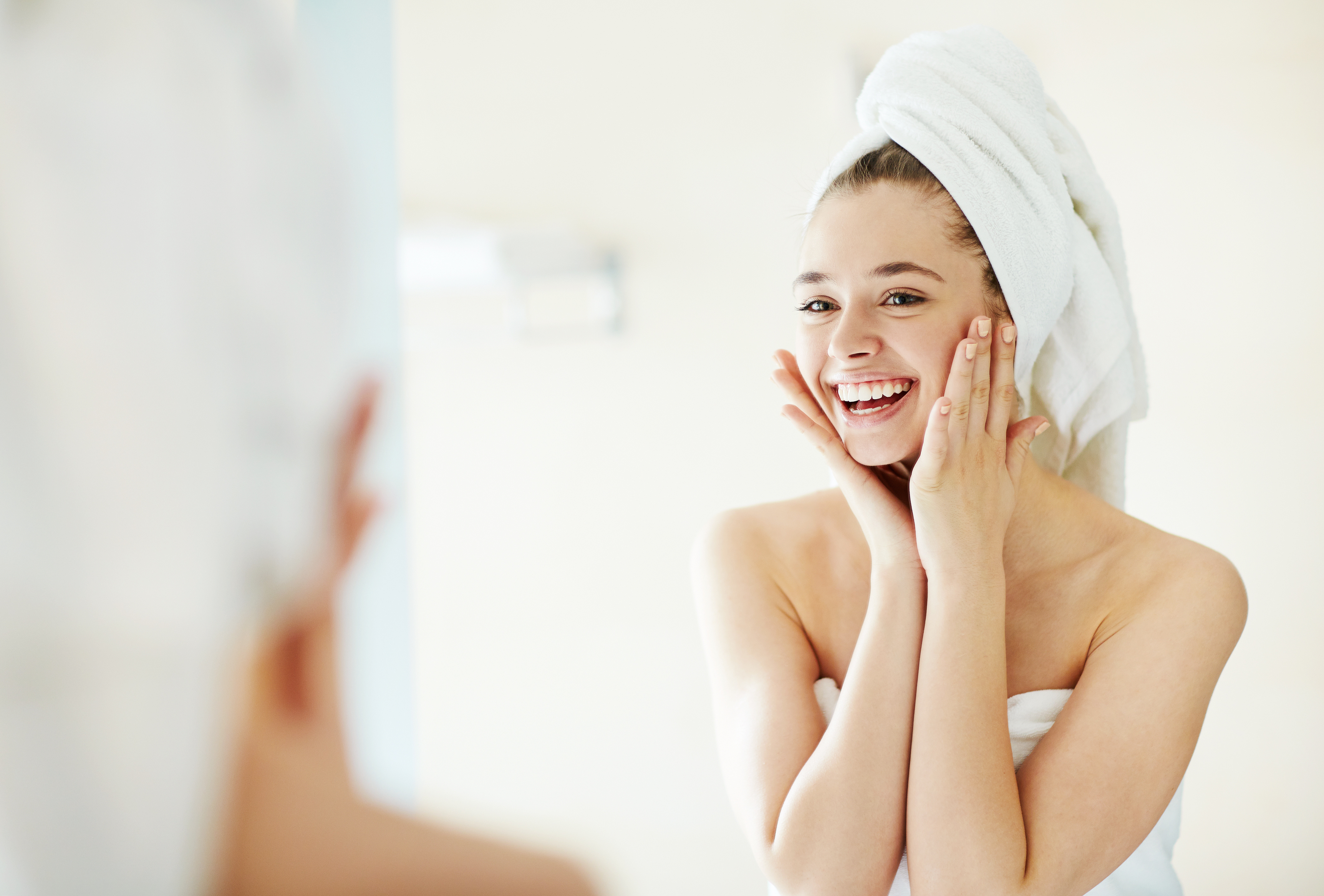 Happy girl looking at her face in mirror after bath